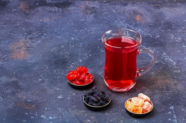 暗い背景にオリエンタルスタイルのドライフルーツ(ハナミズキ、レーズン)とトルコティーカップ(armudu)の赤茶(ルイボス、ハイビスカス、カルカデ)。風邪やインフルエンザのためのハーブ、ビタミン、デトックスティー