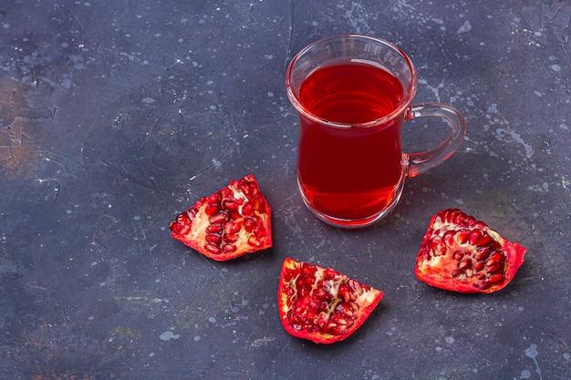 暗い背景にオリエンタルスタイルのザクロとトルコティーカップ(armudu)の赤茶(ルイボス、ハイビスカス、カルカデ)。風邪やインフルエンザのためのハーブ、ビタミン、デトックスティー。テキスト用のコピースペース