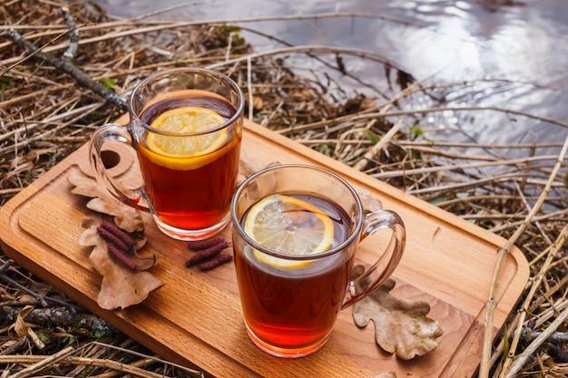 Красный чай с лимоном в стеклянных кружках на природе.