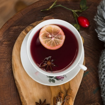 Red tea with lemon slice on wooden pad