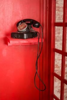 검은색 복고풍 전화기가 서 있는 영국 스타일의 빨간 전화 부스