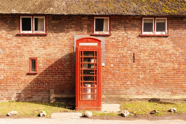 Red telephone booth near a brick wall with windows