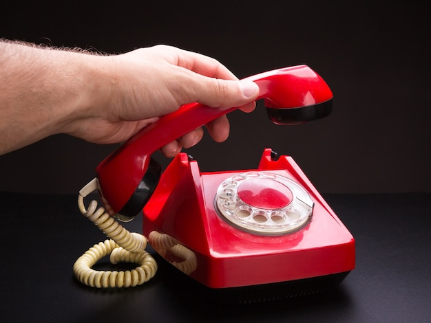 Red telephone handset in hand