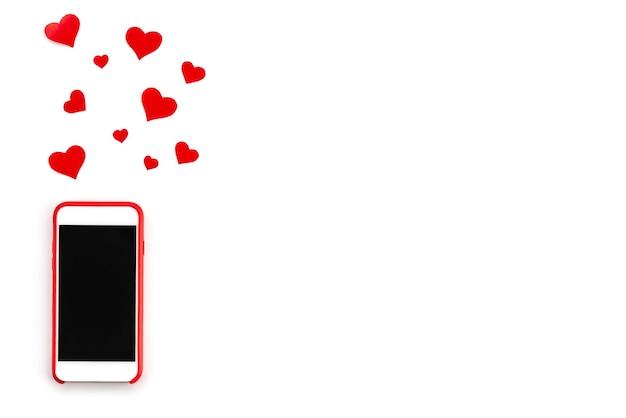 Красный телефон с сердечками на белом фоне.
