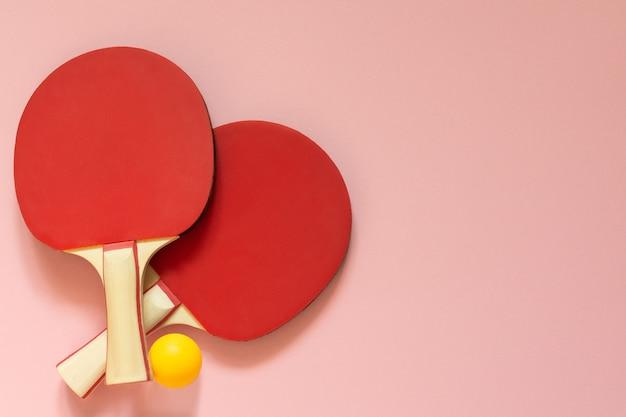 분홍색 배경에 격리된 빨간색 테니스 탁구 라켓과 주황색 공, 탁구용 스포츠 장비