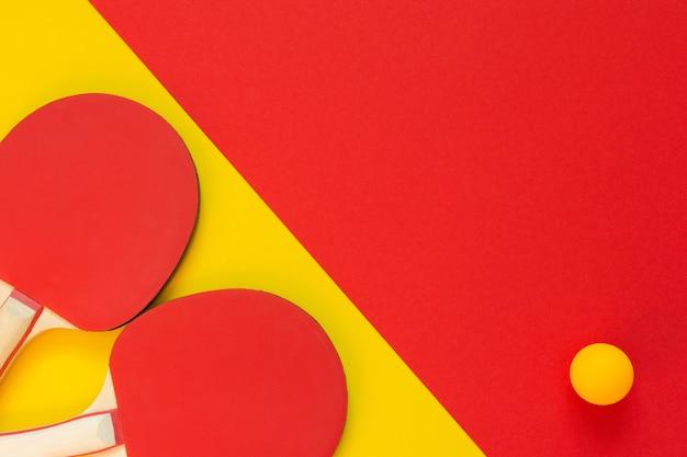 빨간색 테니스 탁구 라켓과 오렌지 공이 빨간색과 노란색 배경에 고립, 탁구 스포츠 장비