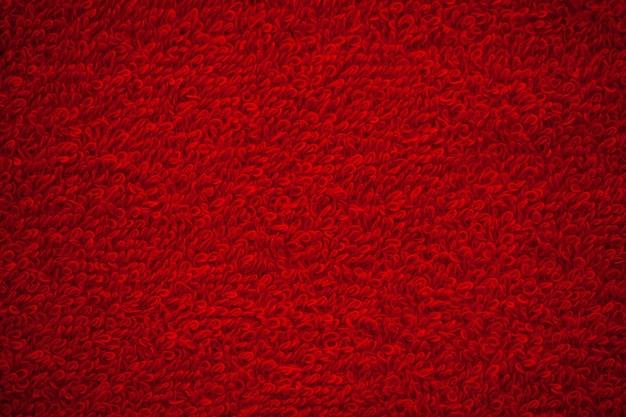 Текстура предпосылки полотенца красного махрового естественного хлопка.