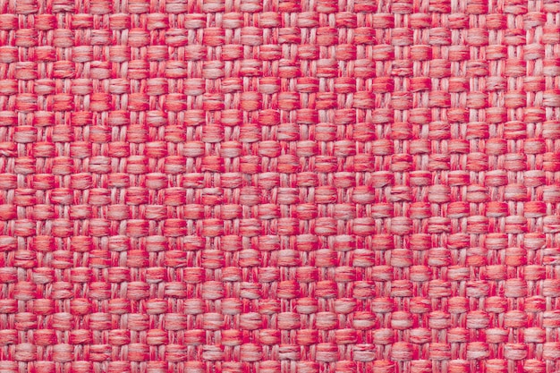 Red textile background with checkered pattern, closeup. structure of the fabric macro.
