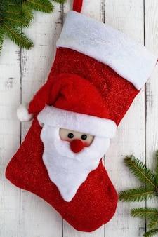 Красный текстильный сапог рождество с головой санты, зеленые ветки ели на белом фоне.