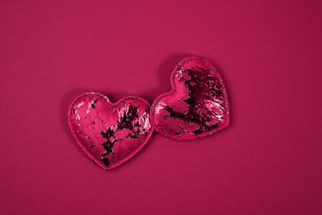 Red textile small hearts on red background, festive background, top view