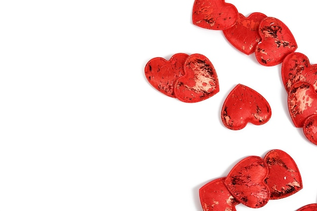 Red textile small hearts on a white background, festive background, copy space