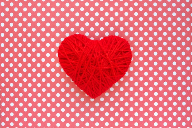 Red thread heart  on background of polka dots textile