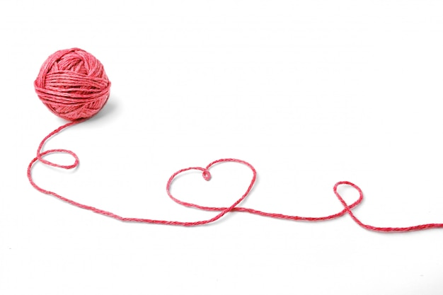 Red thread, heart and tangle on white