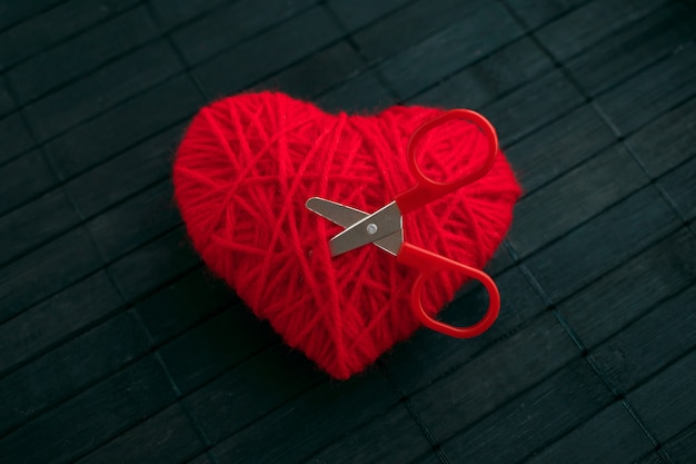 Red thread heart with red stuck scissors