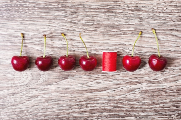 Red thread and ripe red cherries lie on a wooden background, flat lay, top view. conceptual idea, the old grunge background, berries are in a row.
