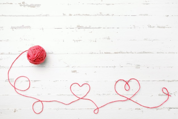 Red thread, two hearts and tangle on light wooden
