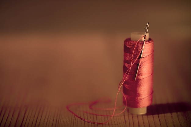 Red thread with needle against wooden background. toned photo