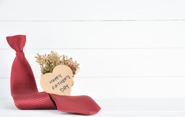 Red tie and brown heart paper with happy father's day text on white wooden.