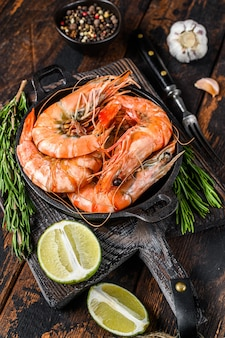 Red tiger shrimps prawns in a pan.  dark wooden background. top view.