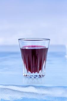 小さなガラスの赤いチンキが氷の上にあります。透明な氷の上のガラスのアルコール。明るい背景がぼやけています。垂直。