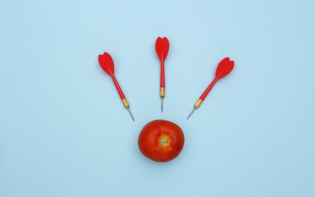 Красный помидор и дротики на синем фоне.
