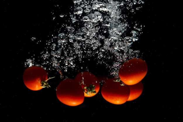Red tomato on black background with water splash