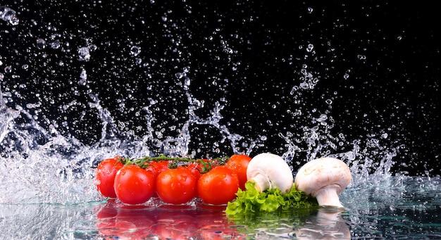 Красный помидор черри, грибы и зеленый свежий салат с каплями воды