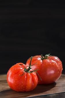 Red tomato on dark wooden board