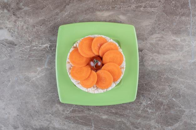 Красный помидор в середине ломтиков моркови и рисовый пирог внизу на тарелке, на мраморной поверхности.