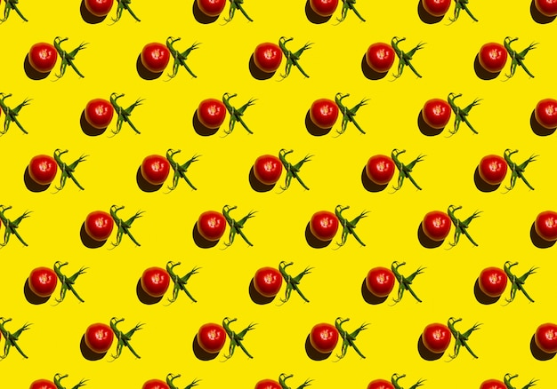 黄色の背景パターンに緑の尾を持つ赤いトマト