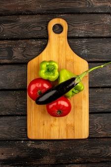 木製の茶色の素朴な床の黄褐色の机の上の緑のピーマンとナスなどの新鮮な熟した野菜の赤いトマトのトップビュー