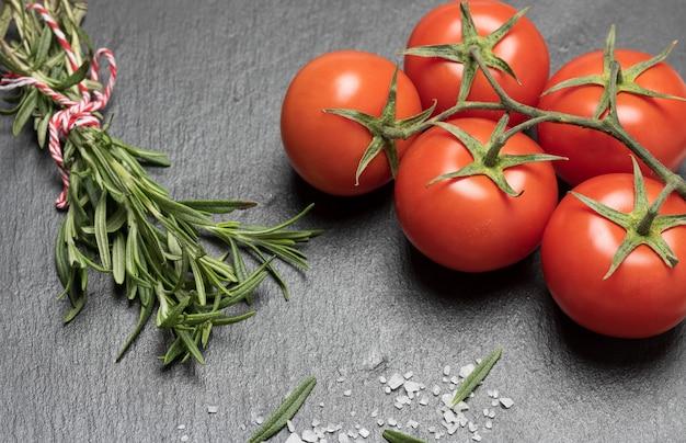 빨간 토마토와 검은 색 표면에 녹색 잎 로즈마리의 신선한 장식을 닫습니다.
