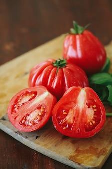 木の板に赤いトマトとミントの葉