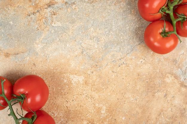 Pomodori rossi ciliegia su un ramo sulla superficie di marmo.