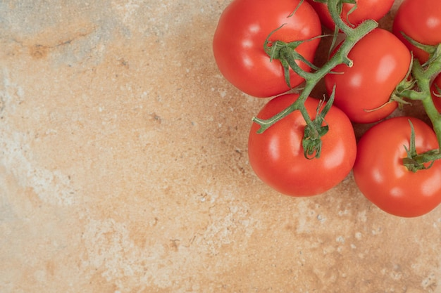 Pomodori rossi ciliegia su un ramo sulla superficie di marmo
