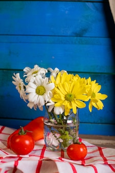 Red tomatoes and a flower vase on blue