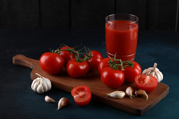 Red tomatoes and garlic gloves on the wooden board with a glass of juice.