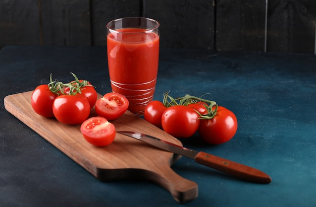 Red tomatoes and a glass of juice on a wooden board with a knife on a blue background.