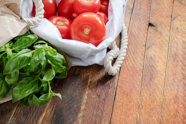 Red tomatoes and green basil in eco-friendly packaging on wooden table.