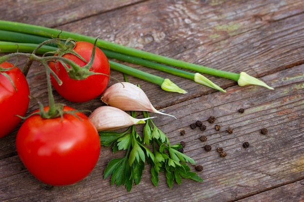 Red tomatoes green onions and garlic and parsley with black peas on a wooden background closeup with...