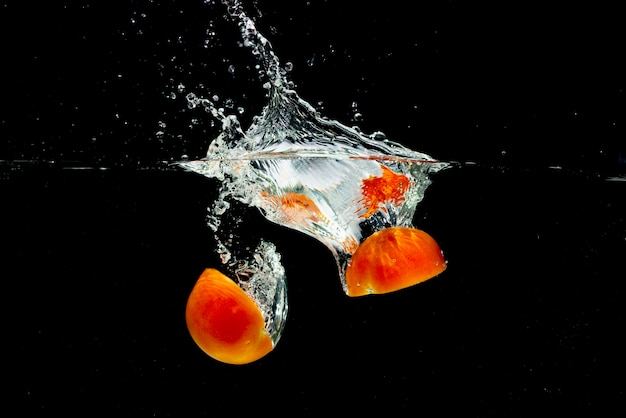 Red tomatoes halves splashing into fresh water