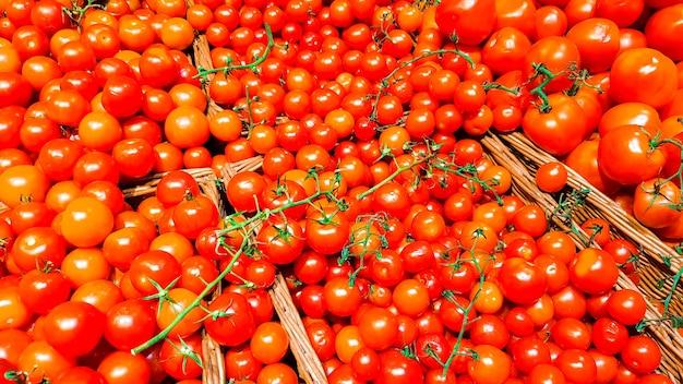 슈퍼마켓의 선반에 있는 상자에 빨간 토마토. 플라스틱 용기 평면도에 꼬리가 있는 빨간 토마토
