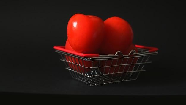 Красные помидоры в корзине супермаркета много