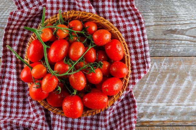 Красные томаты в плетеной корзине на деревянном и кухонном полотенце. плоская планировка