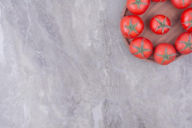 Красные помидоры, изолированные в деревянной тарелке