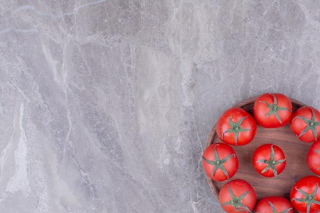 Pomodori rossi isolati in un piatto di legno.