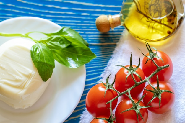 Red tomatoes, mozzarella cheese, olive oil and basil