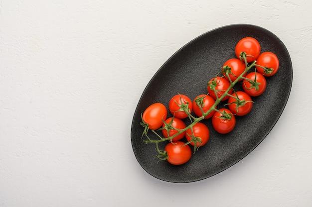 木製の背景の暗い大皿に緑の枝に赤いトマト。
