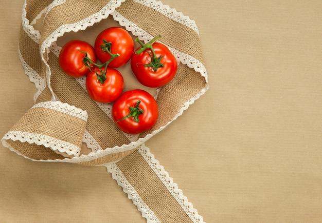 Красные помидоры на коричневой поделке с лентой из мешковины