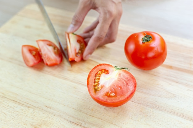 Red tomatoes and slices on wooden cutting board
